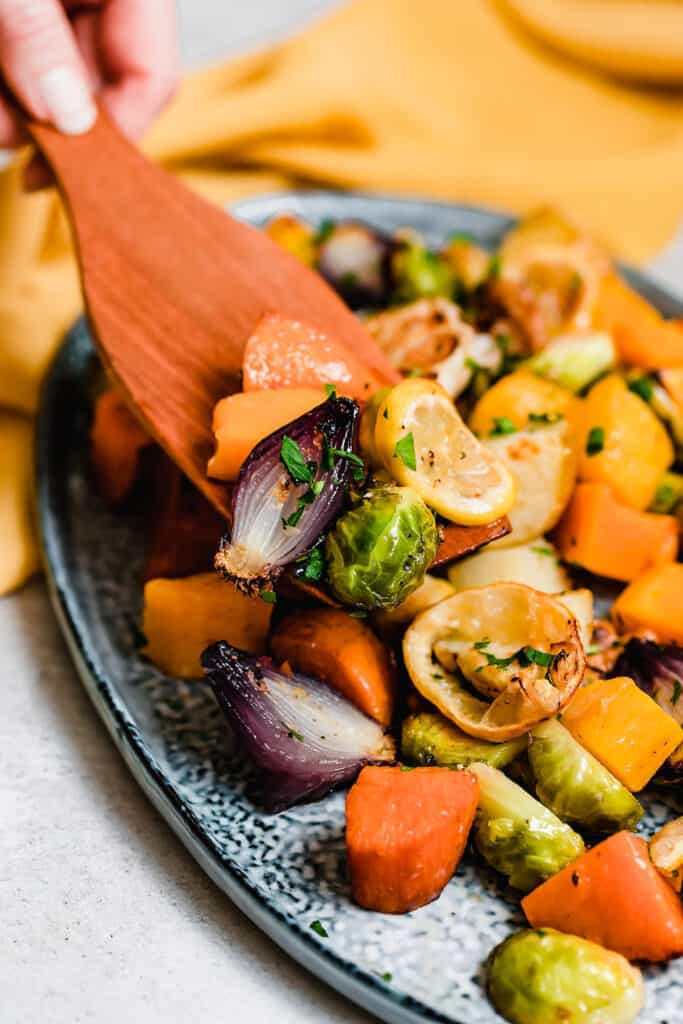 A wooden spoon scooping roasted vegetables off a blue platter.