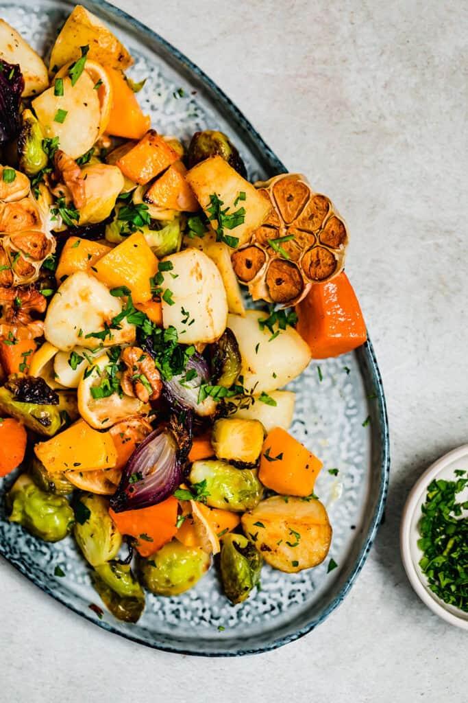 Golden roasted root vegetables on a blue serving platter.