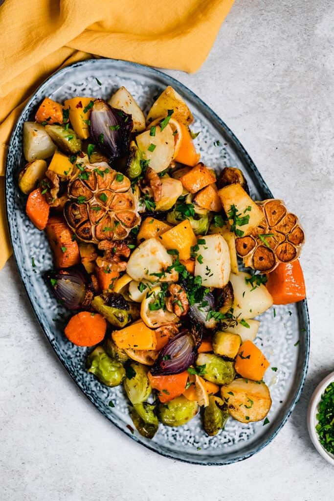 Roasted vegetables on a blue serving platter.