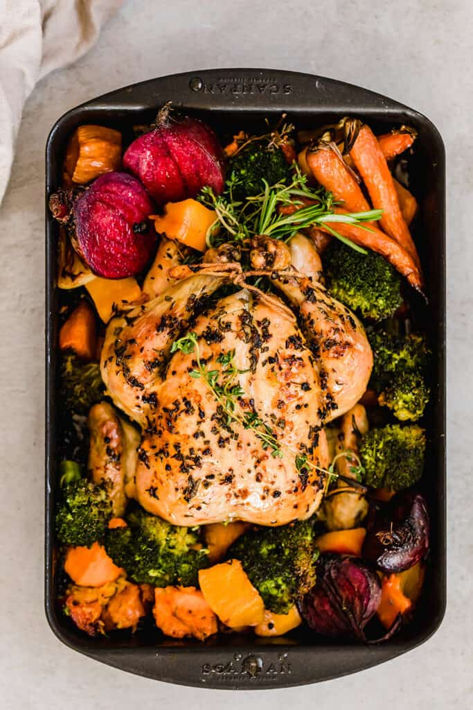 overhead wide shot of whole chicken roasted with fall vegetables in a roasting pan