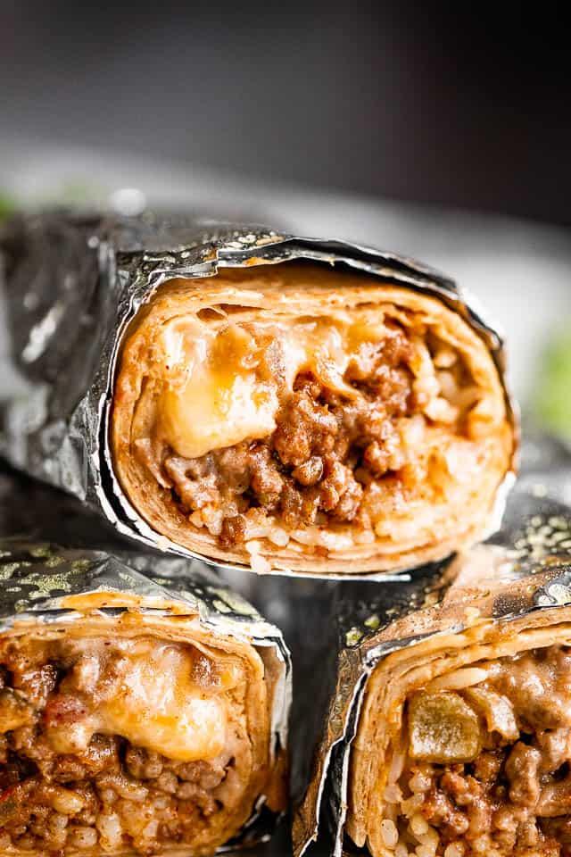close up shot of three cheesy beef burritos cut in half