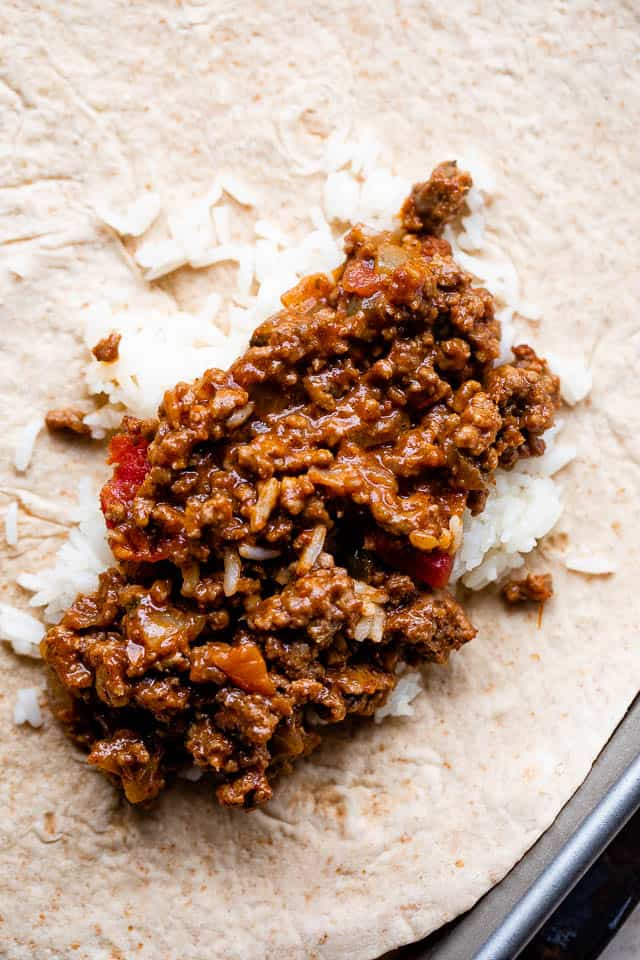 flour tortilla topped with rice and beef