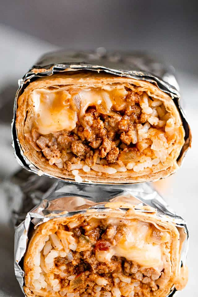 close up shot of two halved burritos stacked one on top of the other