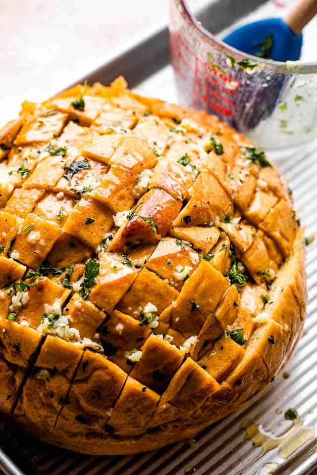 crosshatched loaf of bread with melted butter, garlic, and parsley