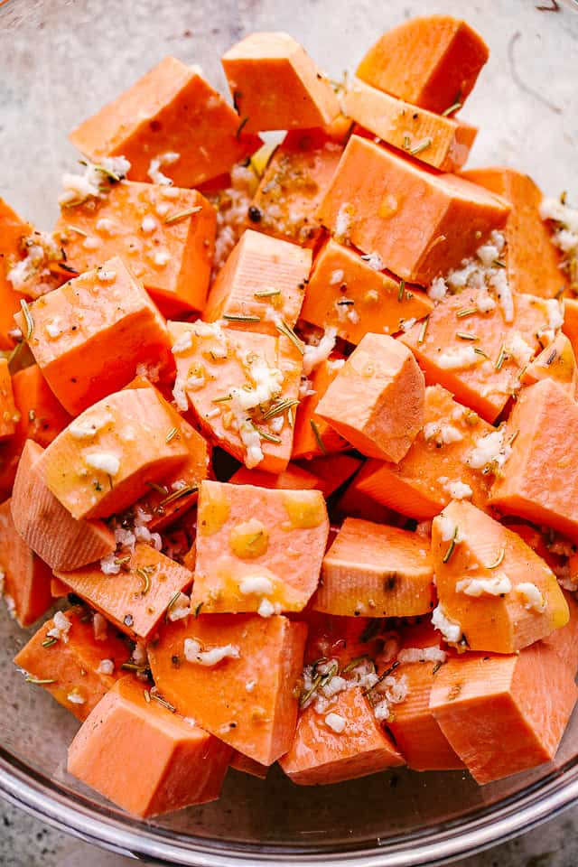 overhead shot of chopped raw sweet potatoes in a mixing bowl