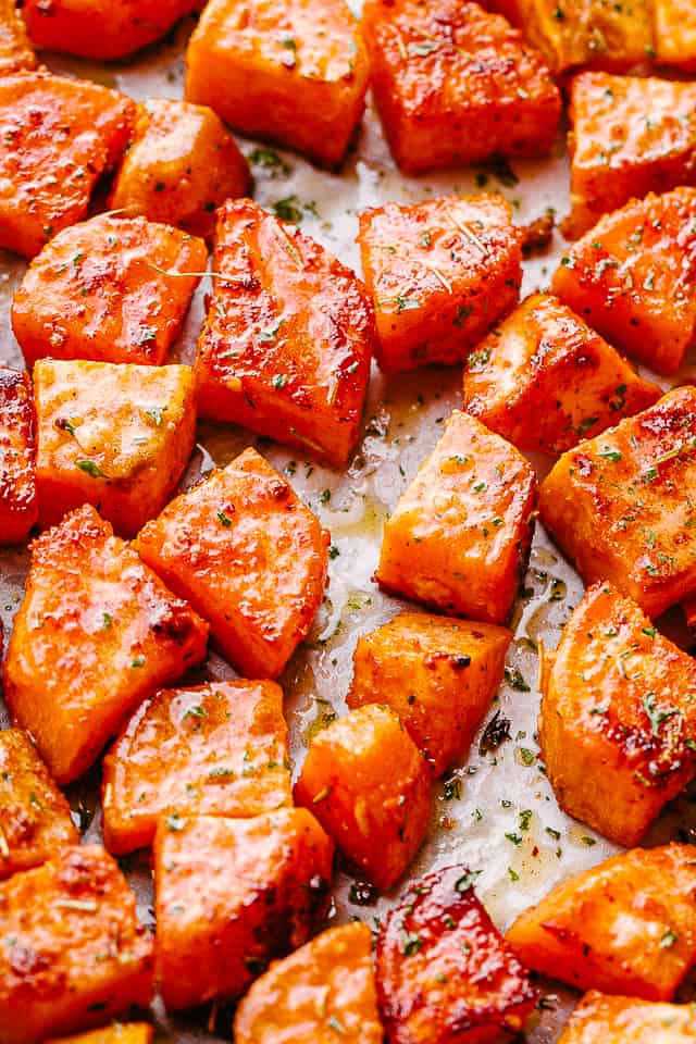 overhead shot of chopped sweet potatoes on parchment paper