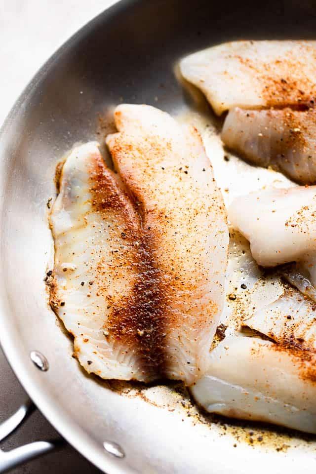 cooking tilapia fillets in a skillet