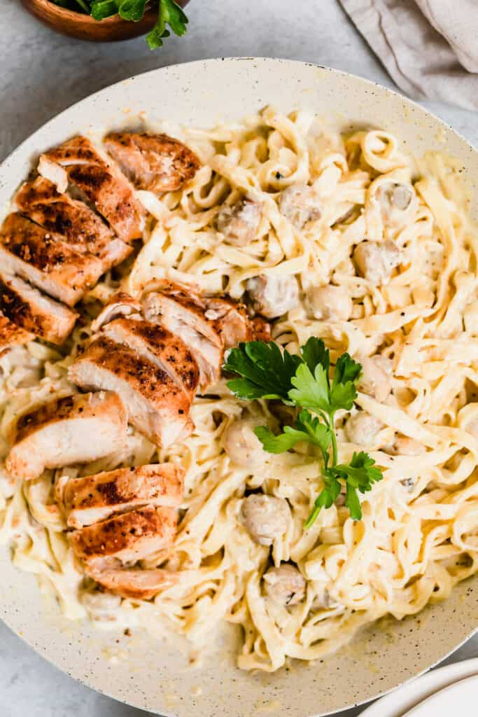 Chicken Fettuccine Alfredo in a Large Bowl, Garnished with Parsley