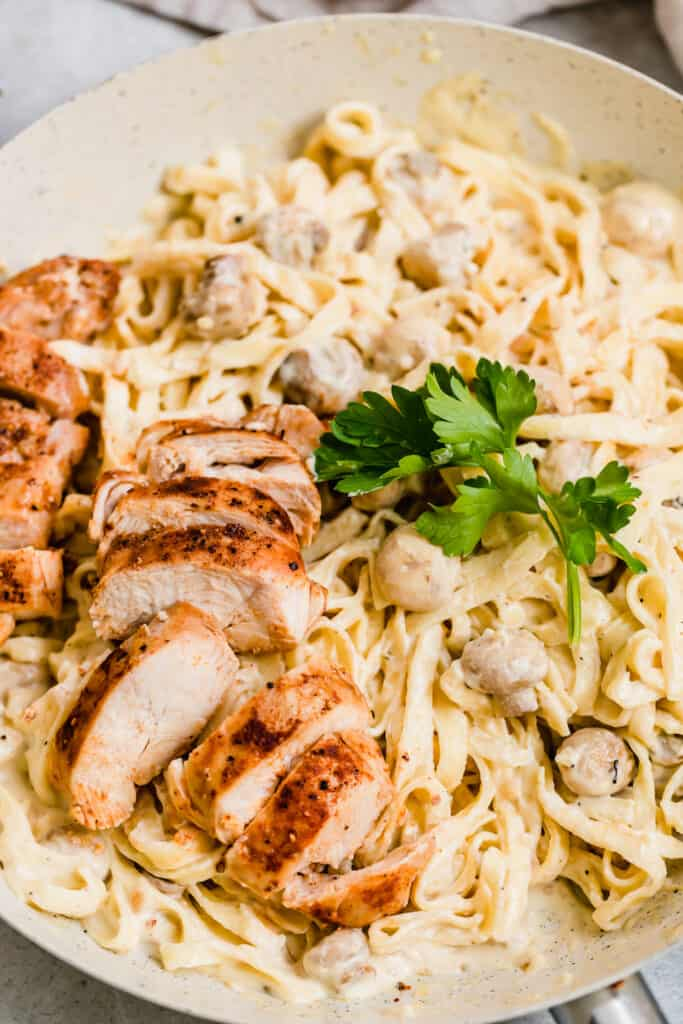 Chopped Chicken and Fresh Parsley over a Bowl of Alfredo Pasta