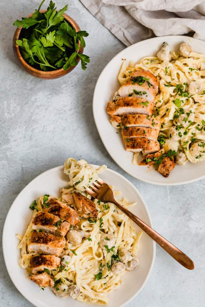 Two Bowls of Chicken Fettuccine Alfredo Next to a Small Container of Parsley Leaves