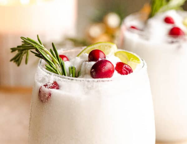 drinking glasses filled with white frozen margaritas and garnished with lime slices, rosemary sprigs, and cranberries