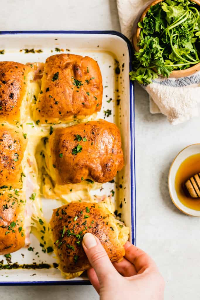 Six Cheesy Ham Sandwiches in a Navy Blue and White Baking Dish