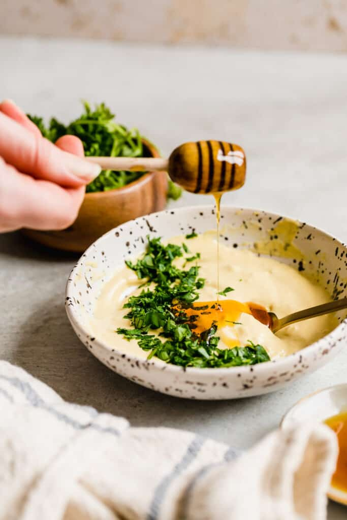 Fresh Honey Being Added to the Mayo and Parsley Mixture