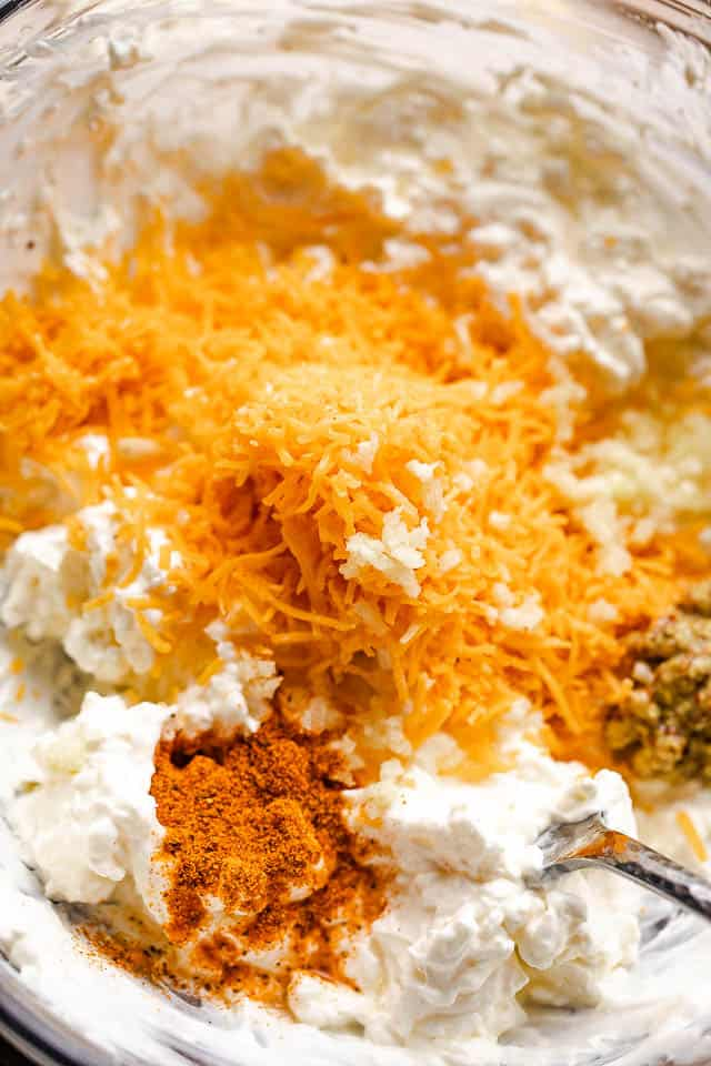 cream cheese, seasonings, and shredded cheese in a mixing bowl