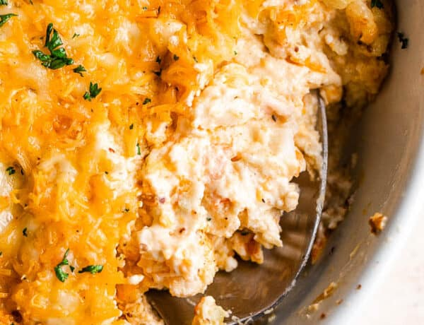 close up shot of a spoon in a baking dish with hot crab dip