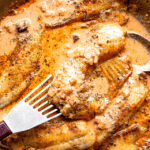 picking up tilapia fillet with a fish spatula