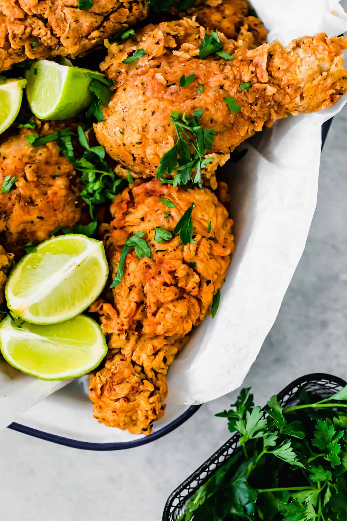 A Basked of Buttermilk Fried Chicken with Lime Wedges Inside