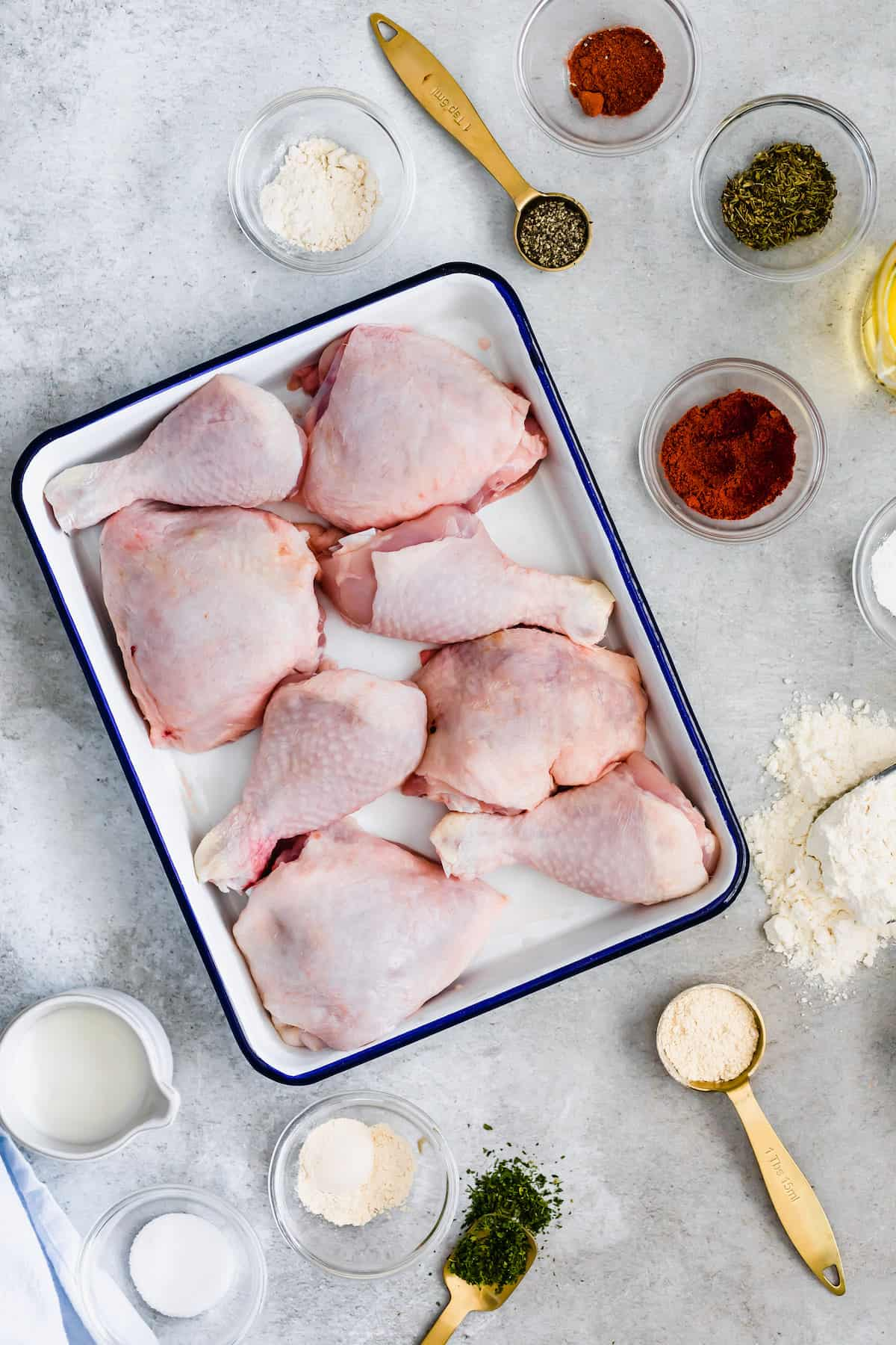 Eight Chicken Thighs and Drumsticks in a White and Blue Pan Surrounded by Herbs, Spices and Buttermilk