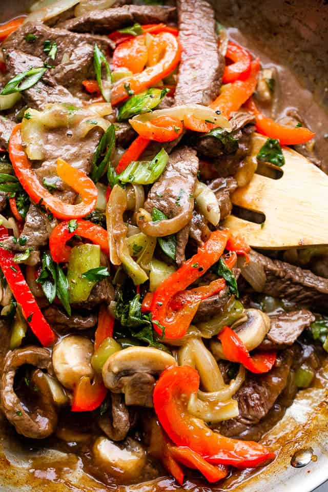 stirring through beef stir fry with vegetables