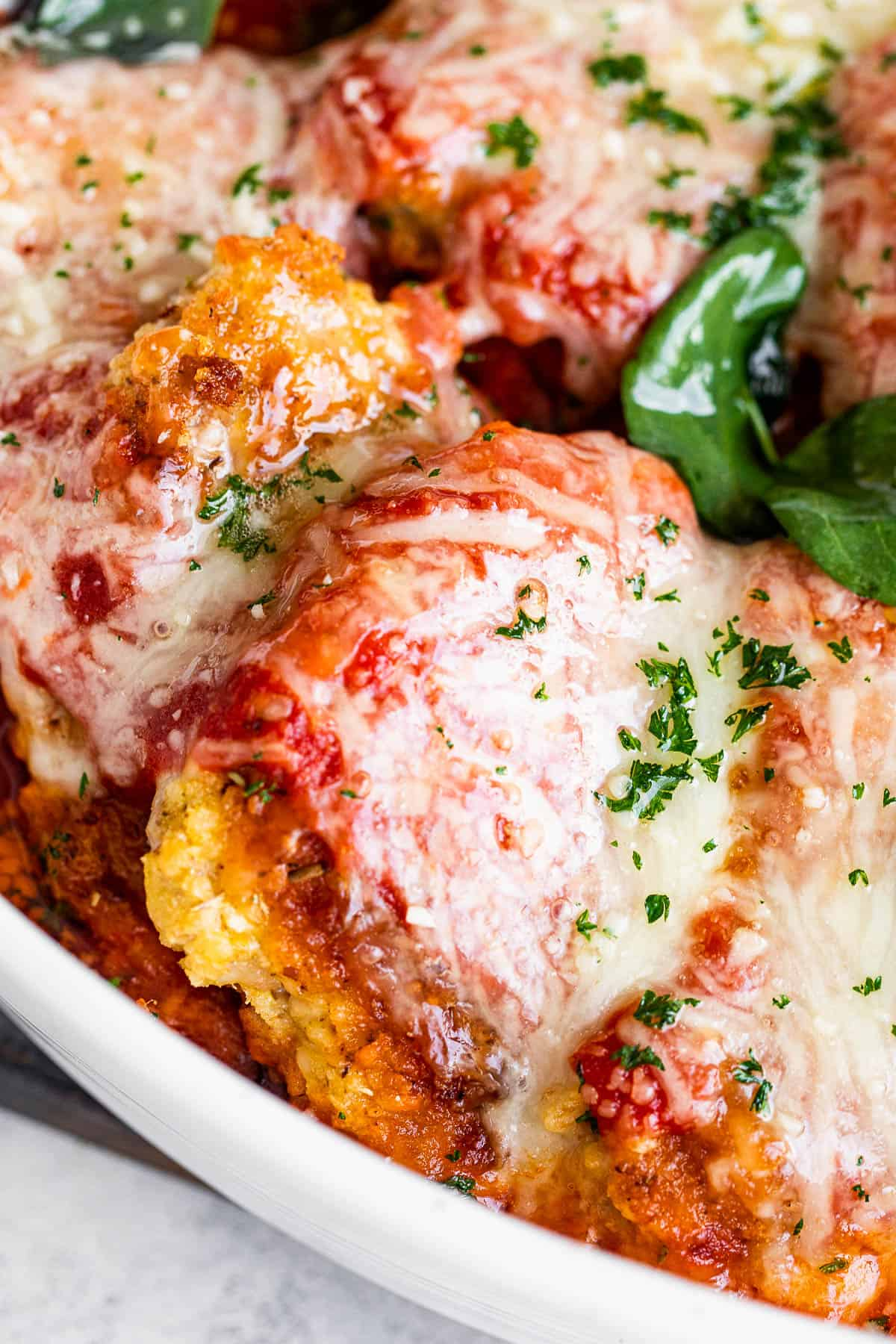 close up shot of baked pork parmigiana topped with melted cheese and basil leaves.