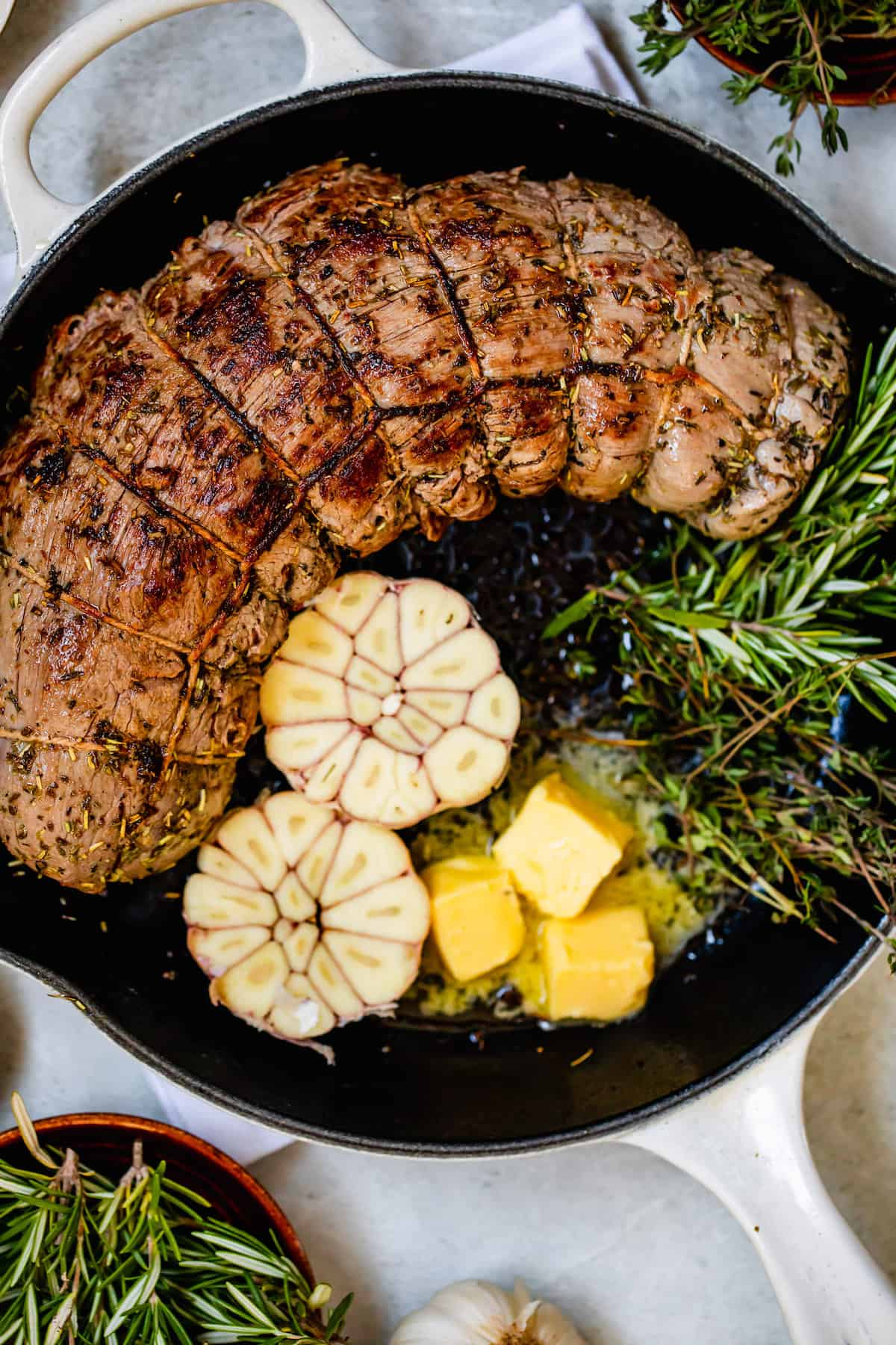 Roast Tenderloin, Garlic Cloves, Rosemary and Butter in a Metal Skillet