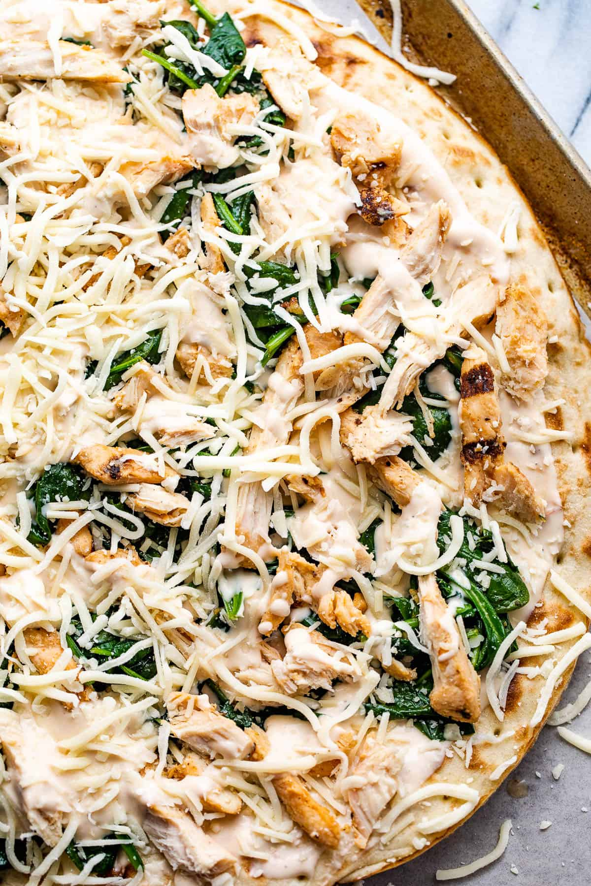 preparing pizza with alfredo sauce, shredded chicken, spinach, and cheese