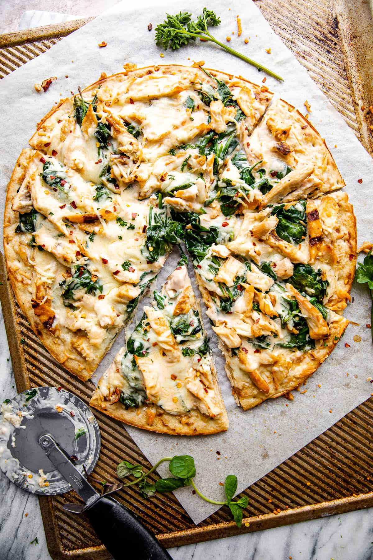 overhead shot of homemade chicken alfredo pizza with pizza cutter placed next to the pizza
