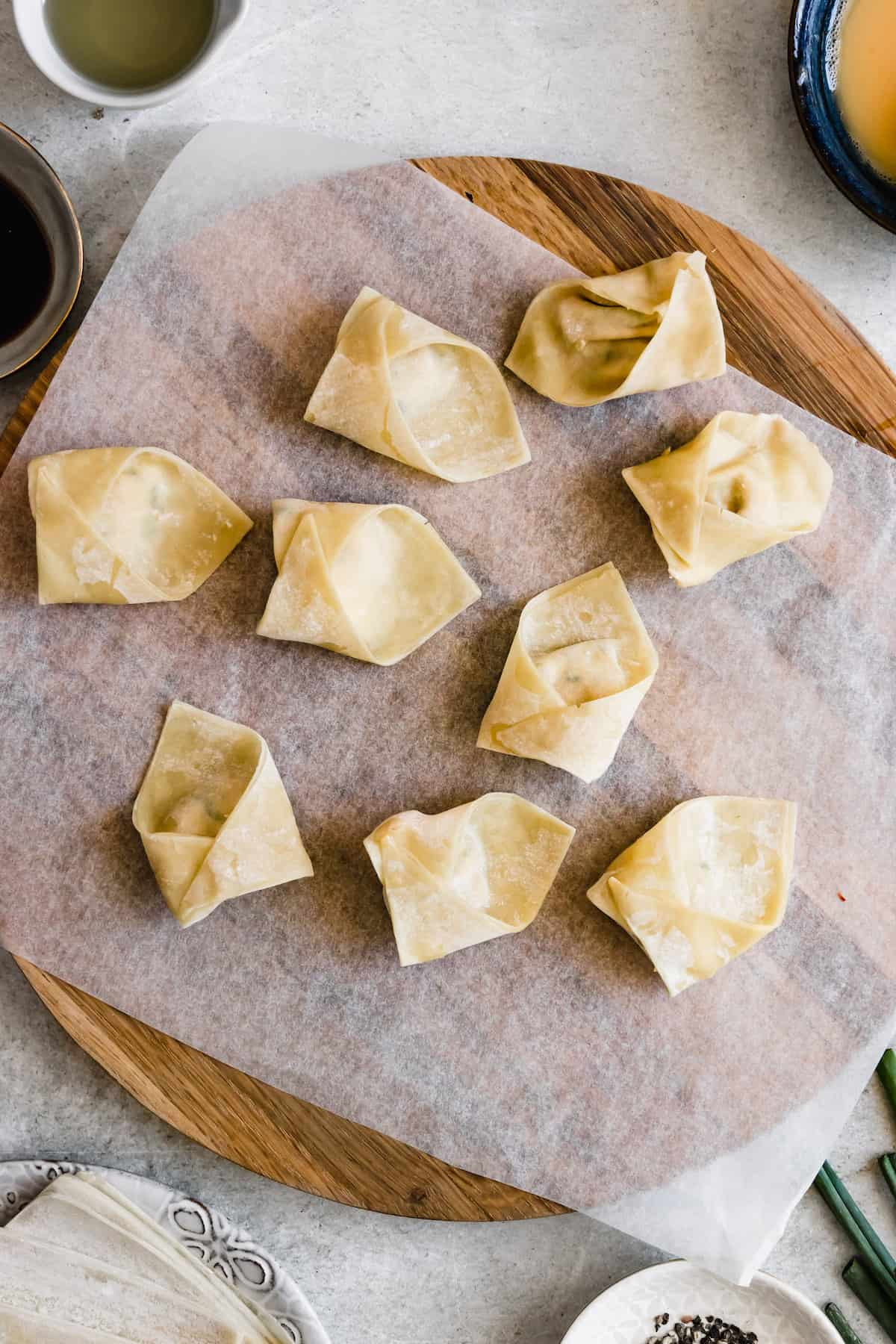 Filled and wrapped wonton wrappers and set on a cutting board.