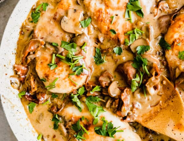 Chicken marsala in a white pan with a wooden spoon