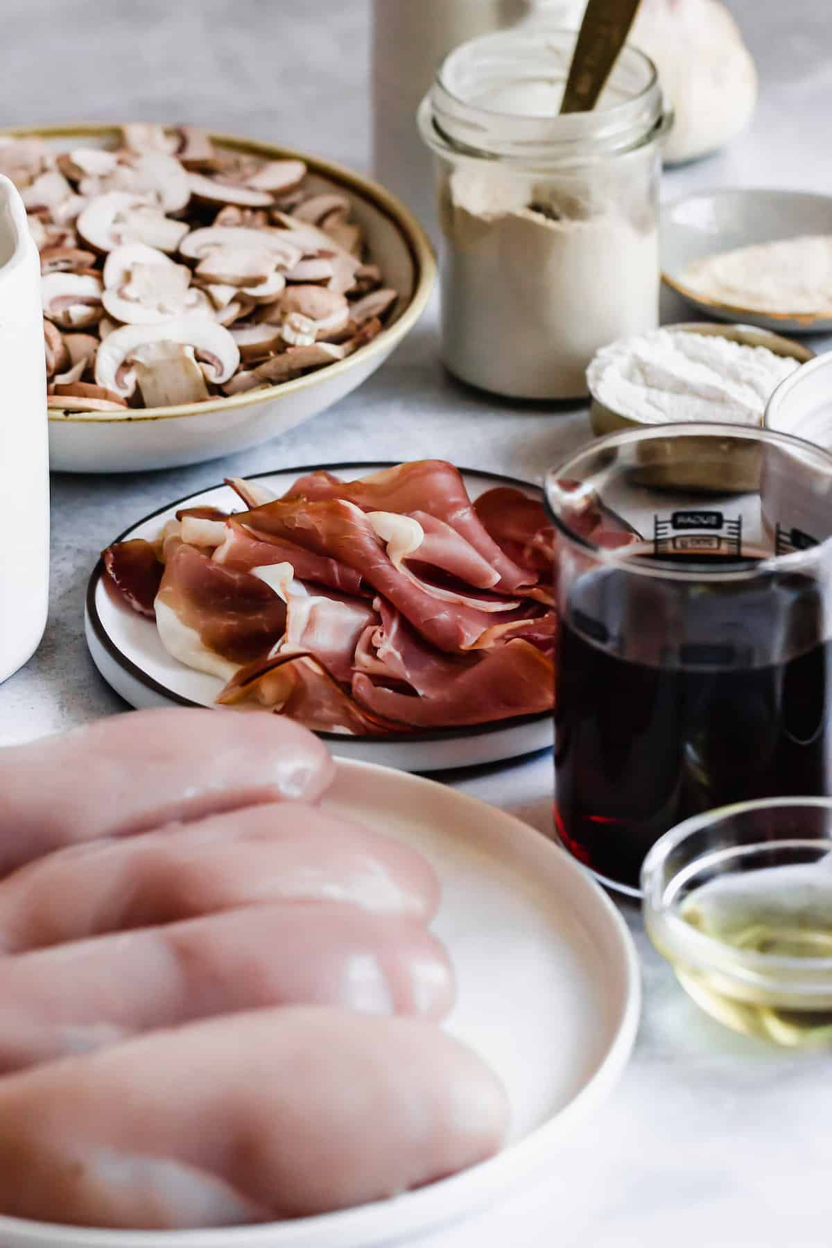 A plate of sliced white mushrooms, a plate of proscuitto, a cup of flour, and a cup of marsala wine.