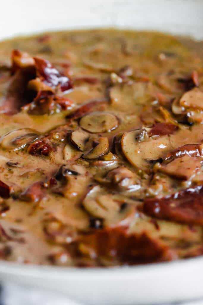 Mushrooms and proscuitto cooking in a creamy sauce.