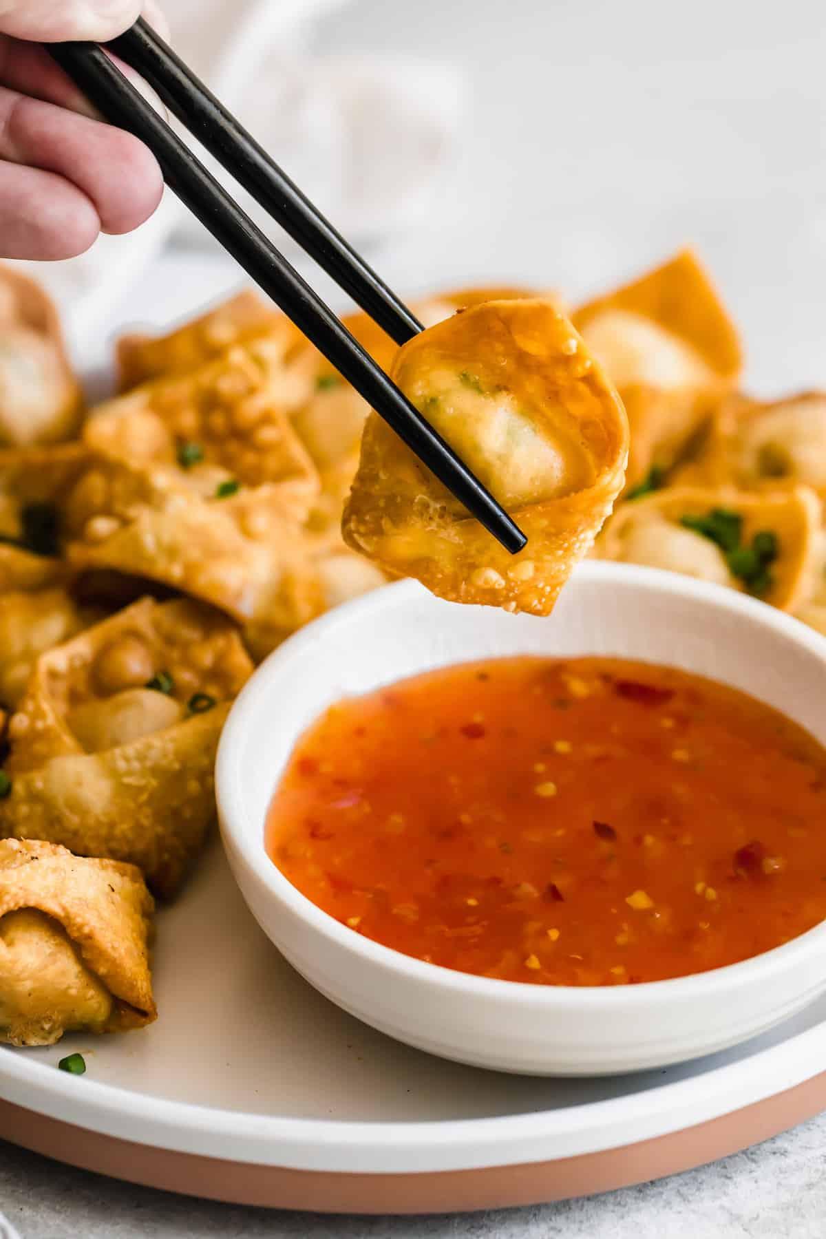 holding chopsticks and dipping crab rangoon wonton in dipping sauce