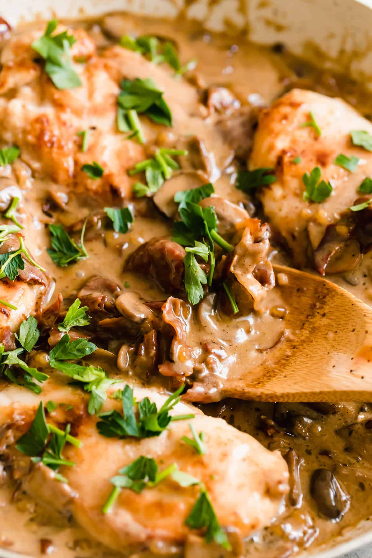 Close up of mushrooms cooking in a creamy marsala sauce with fresh herbs sprinkled on top.
