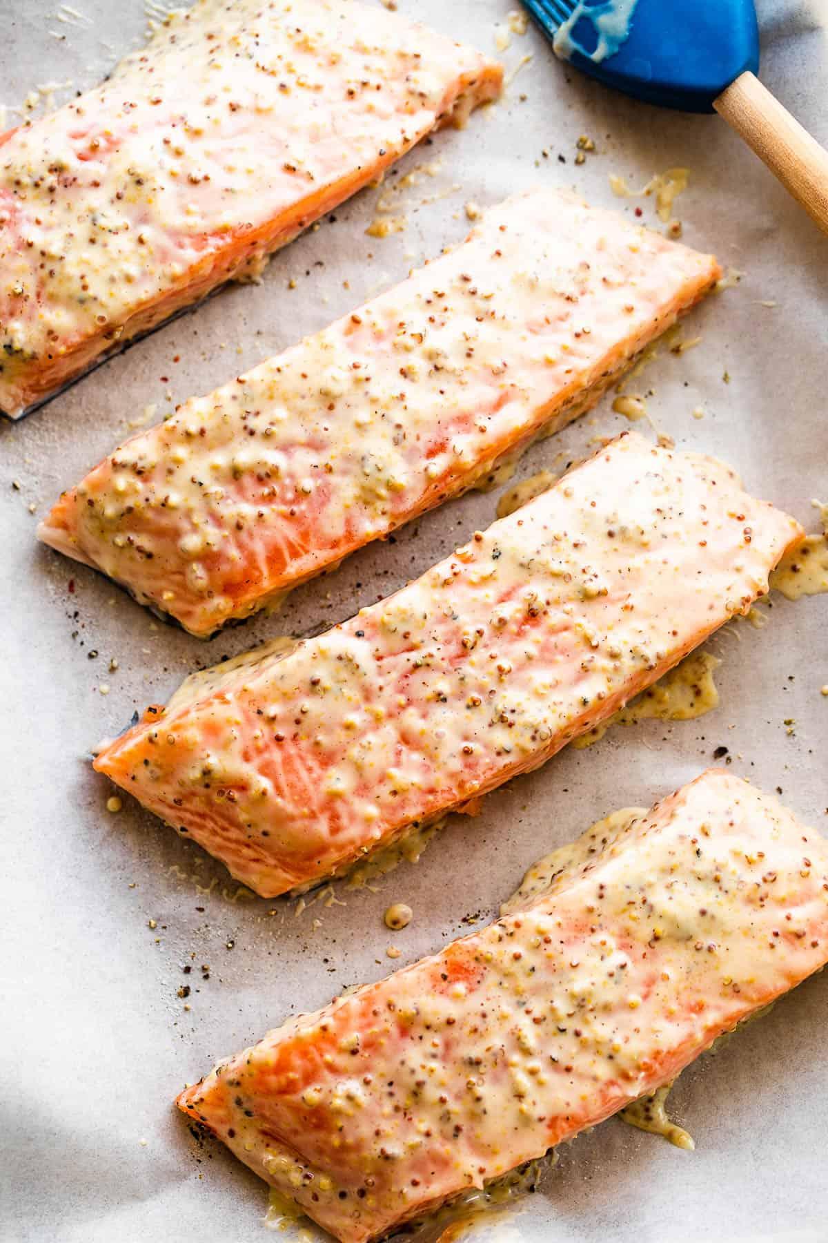 four raw salmon fillets arranged on a baking sheet