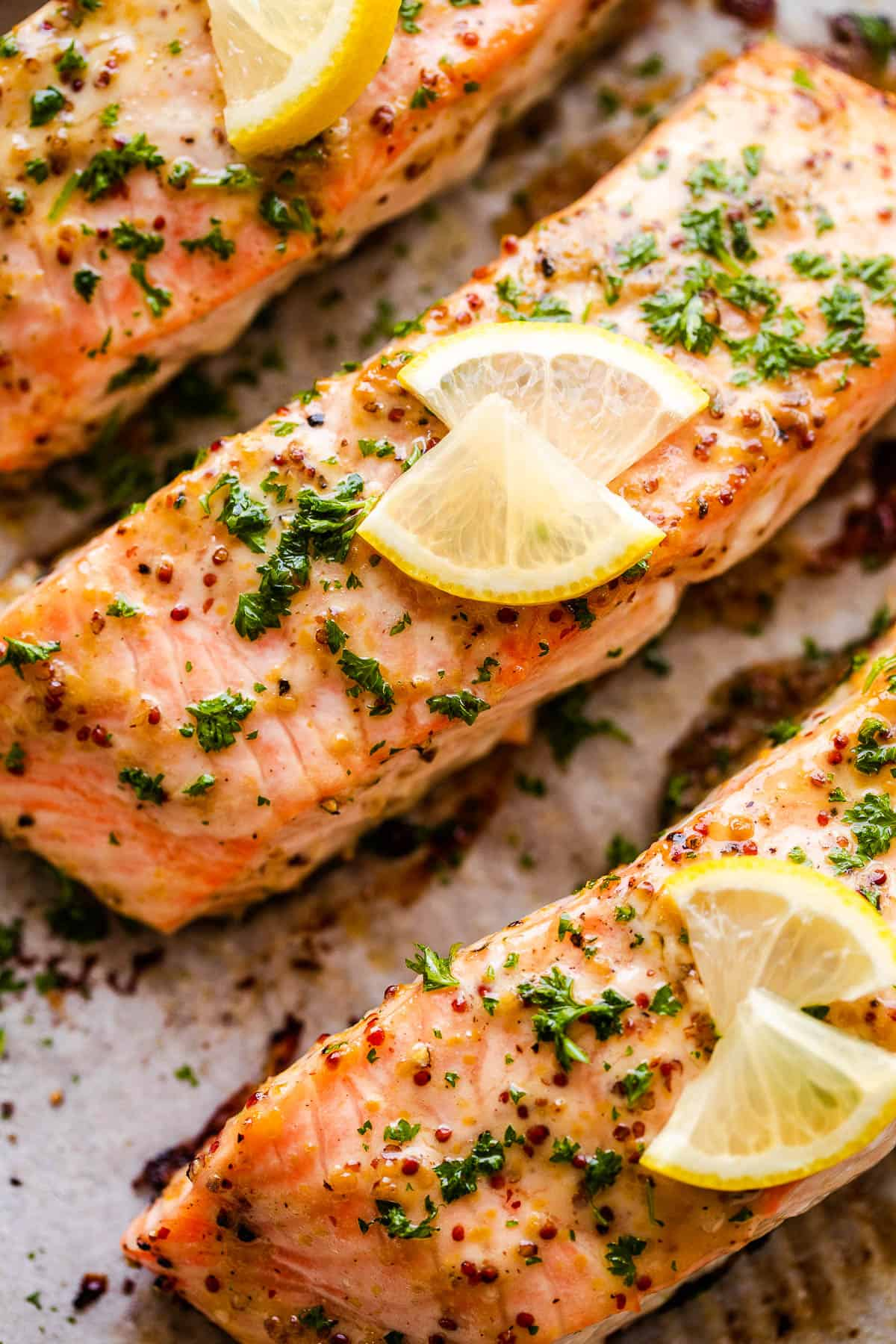 up close photo of maple mustard salmon fillets garnished with parsley and lemon slices