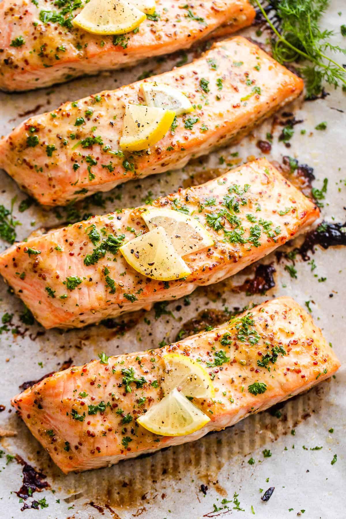 four maple mustard salmon fillets arranged on a baking sheet