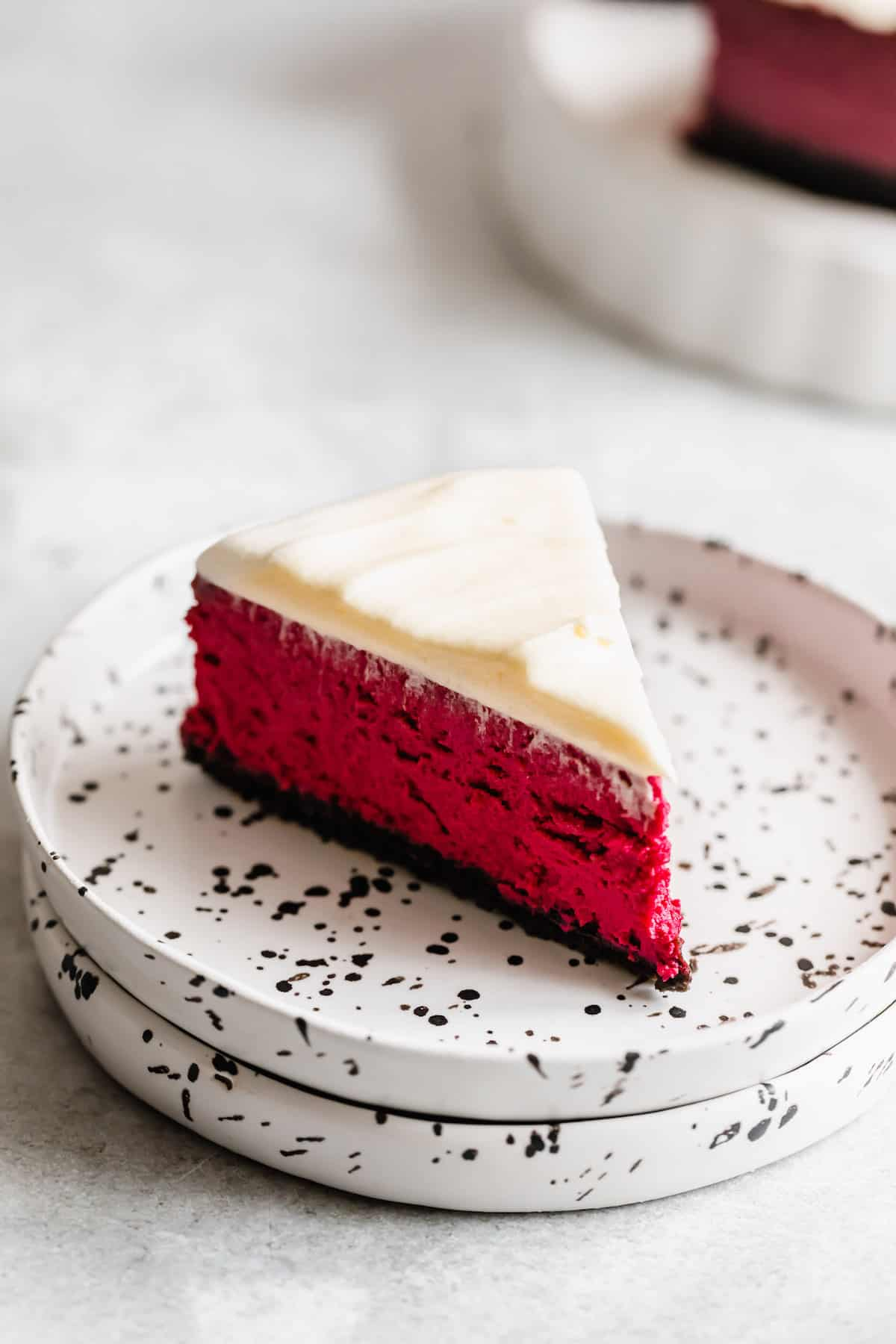 A Slice of Homemade Cheesecake with Oreo Crust and Cream Cheese Frosting on a Dessert Plate