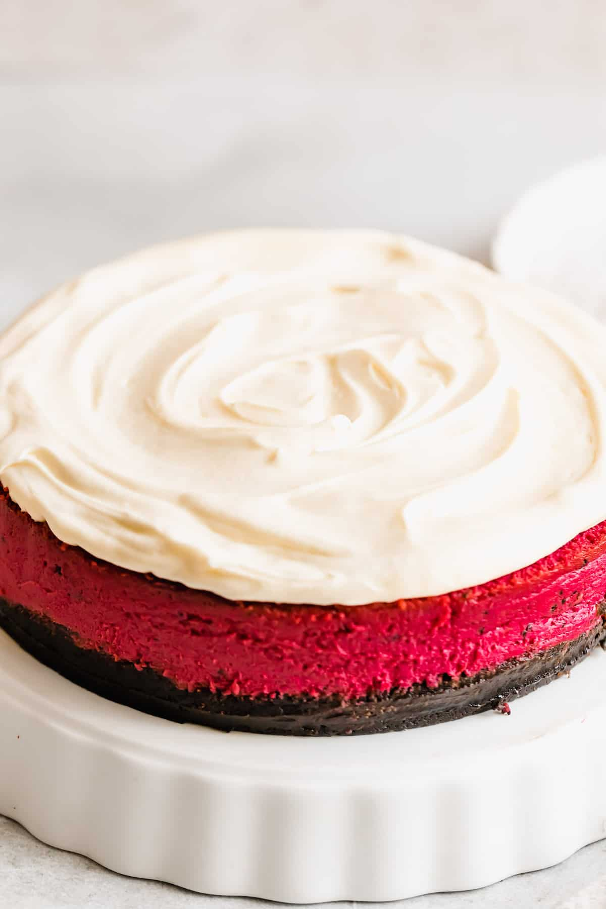 A Close-Up Shot of a Red Velvet Cheesecake Frosted with Homemade Cream Cheese Icing