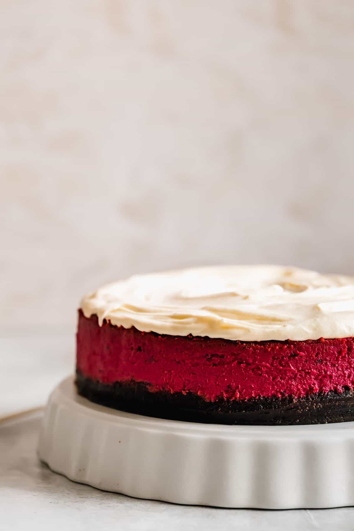 A Vibrant Red Velvet Cheesecake on a Cake Stand with a White Background
