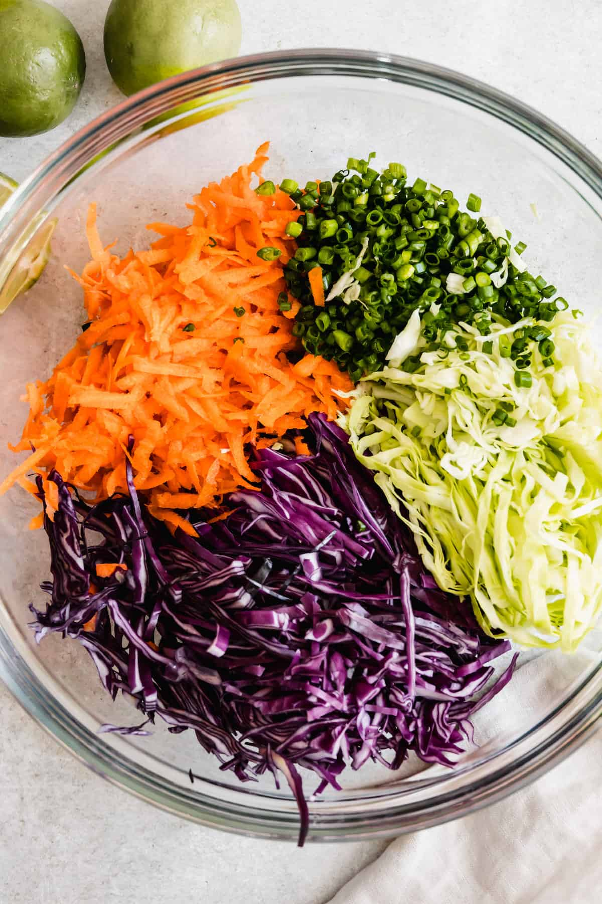 A Bowl Filled with the Cabbage Slaw Ingredients Beside Two Limes and Half of Another Lime