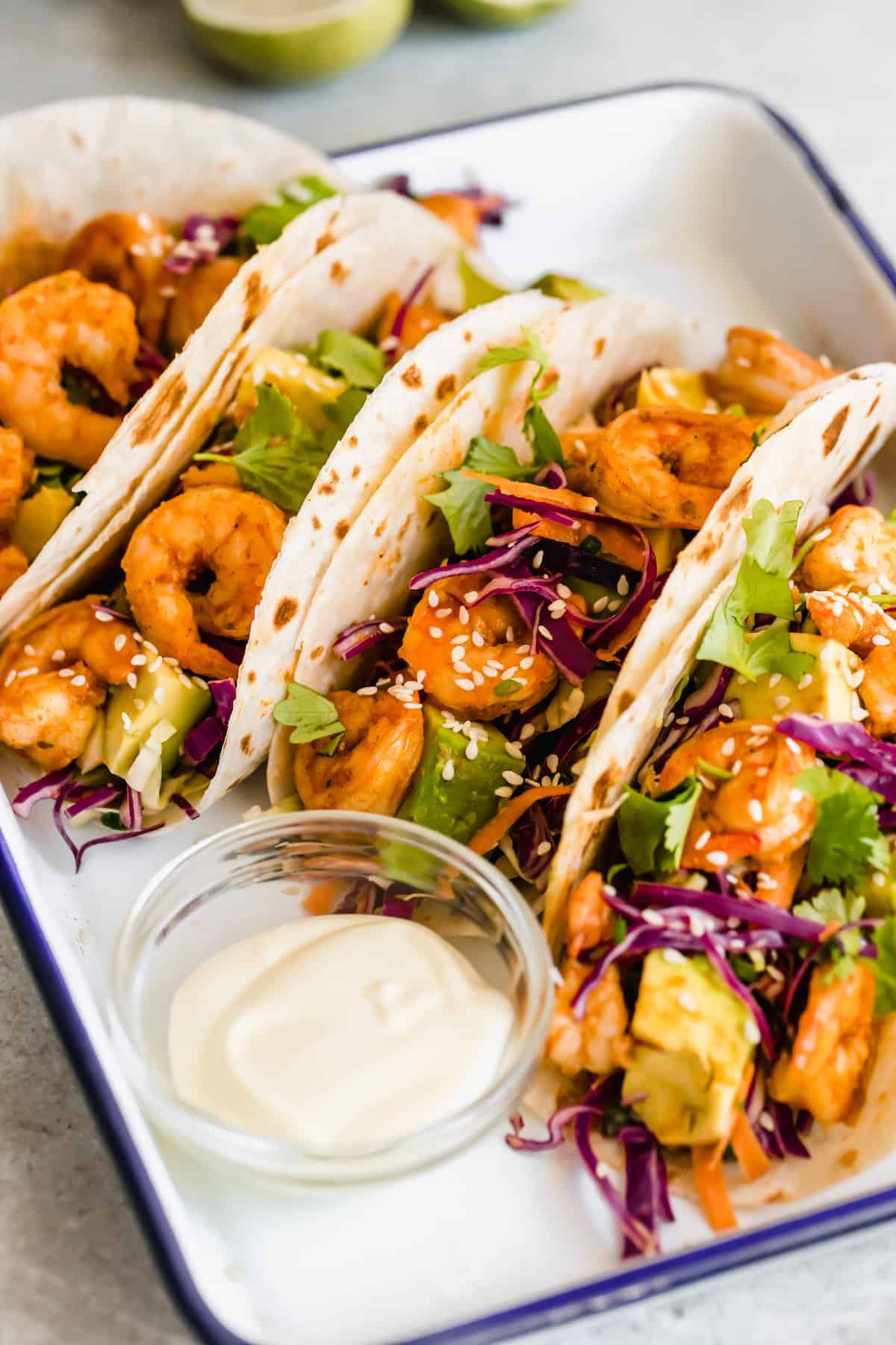 A Platter Holding Four Shrimp Tacos and a Dish of Dressing