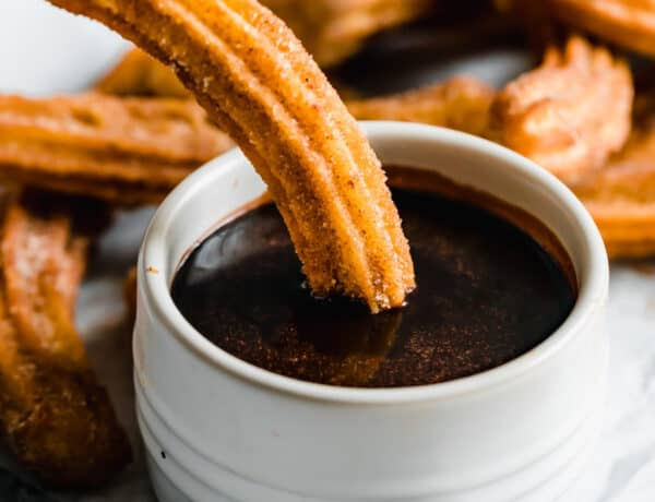A Homemade Churro Being Dipped Into a Dish of Chocolate Sauce