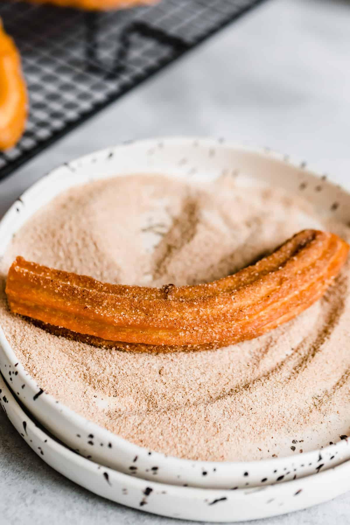 A Churro Inside a Shallow Bowl Filled with Cinnamon Sugar