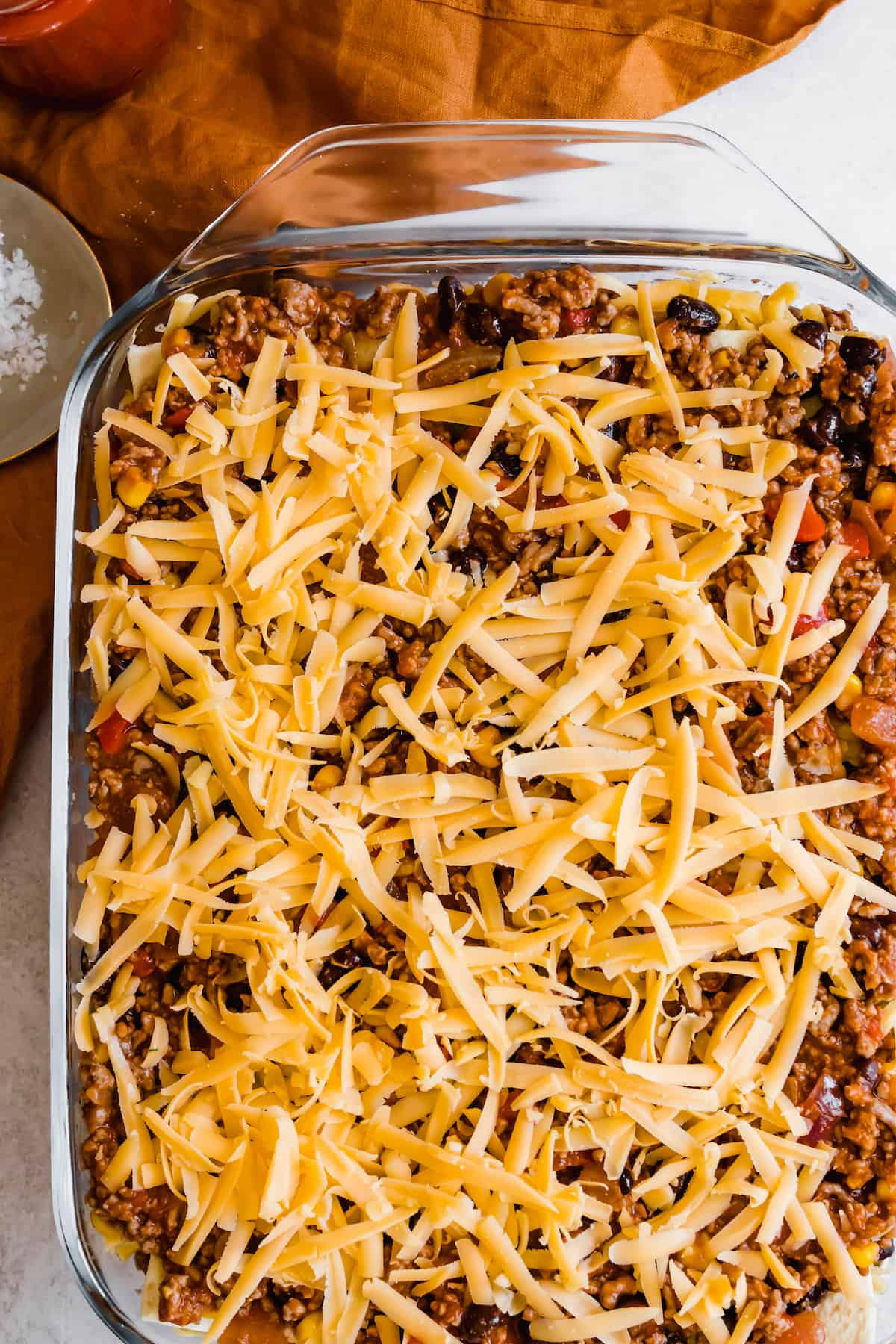 Layered, Unbaked Mexican Lasagna with Shredded Cheddar Cheese on Top
