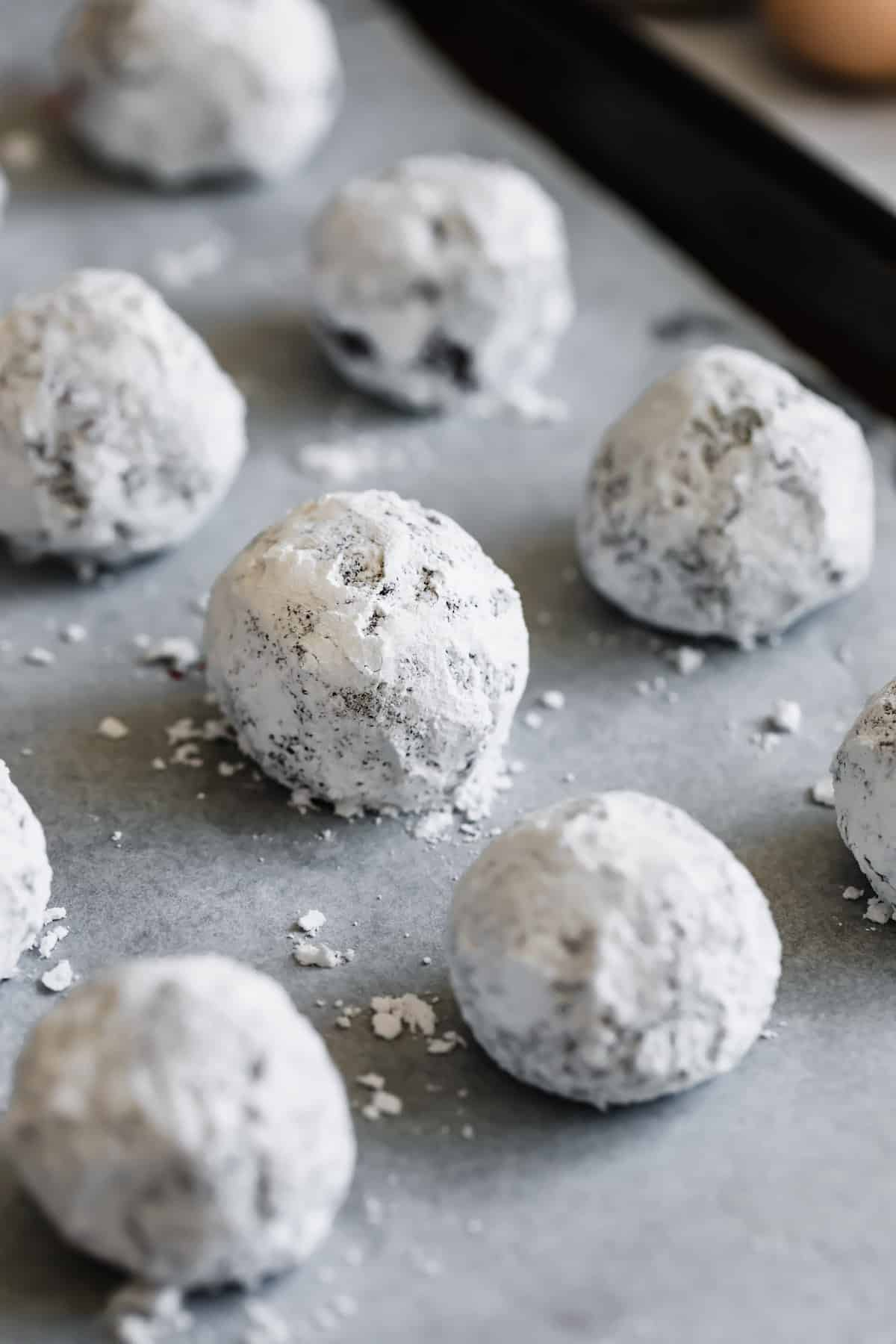 A Parchment-Lined Baking Sheet with Powdered Sugar-Dusted Balls of Dough On it