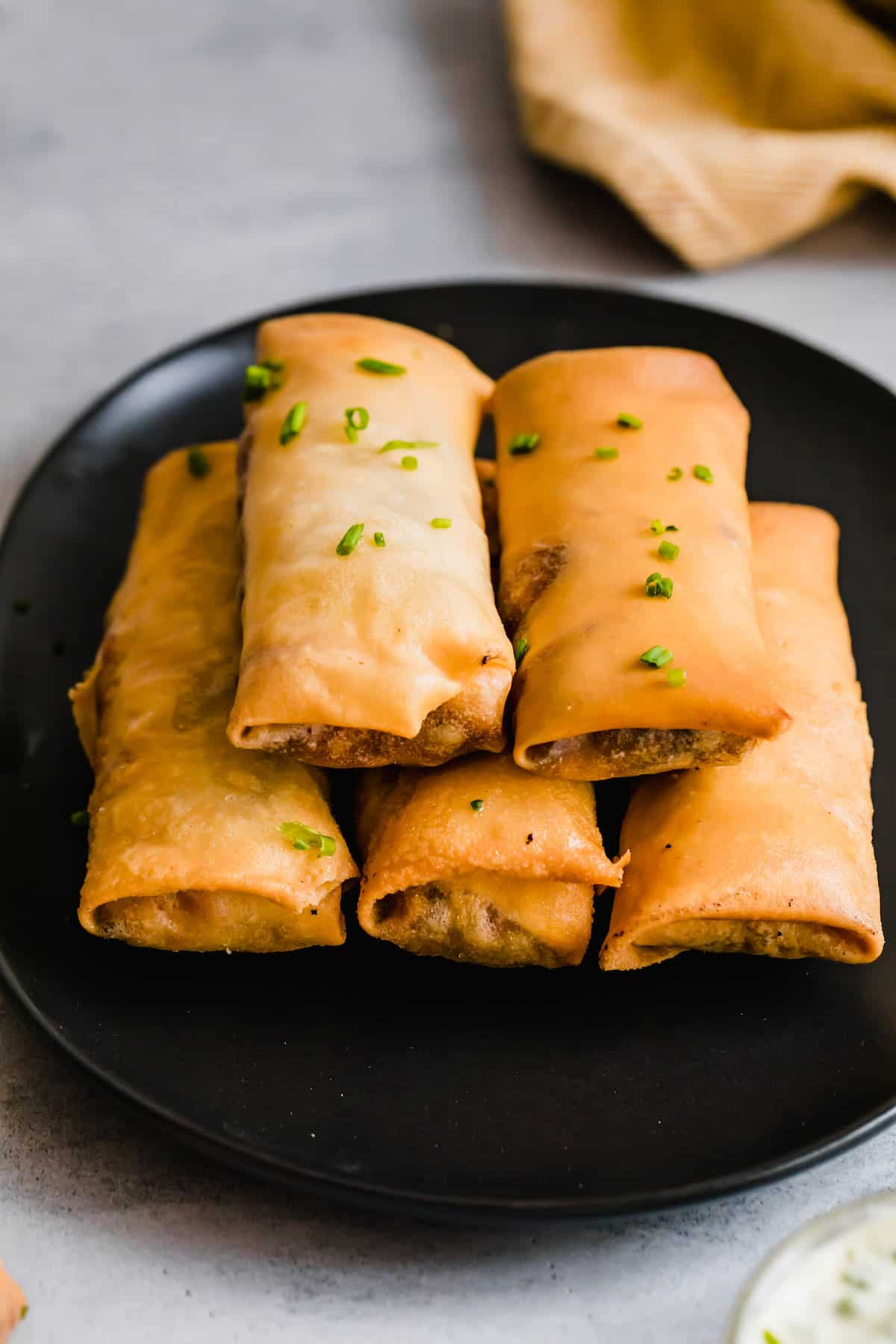 Five Egg Rolls Piled Neatly on a Shiny Black Plate