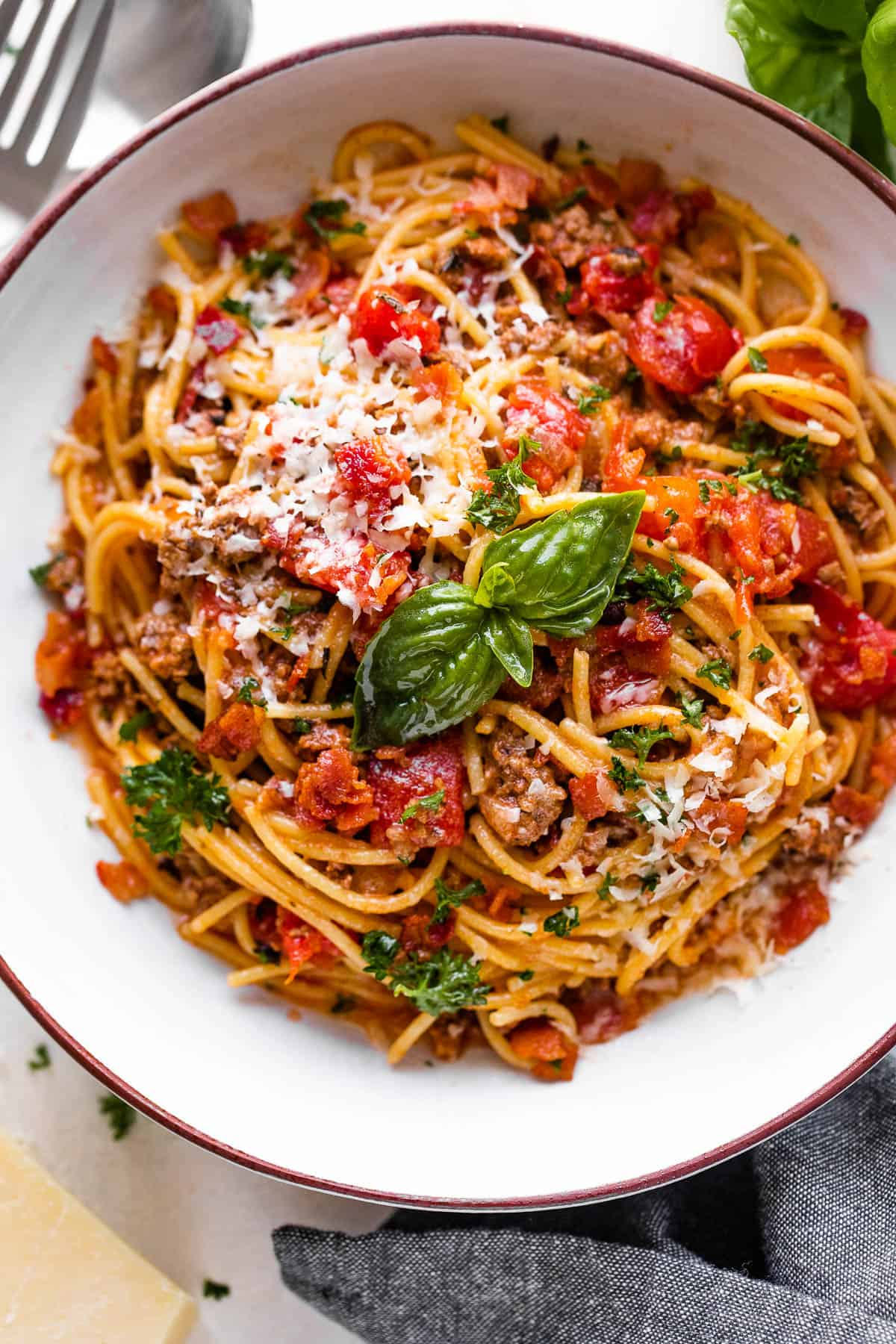 overhead shot of a spaghetti bowl topped with tomatoes and basil
