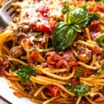 close up shot of spaghetti with ground beef, tomatoes, and fresh basil