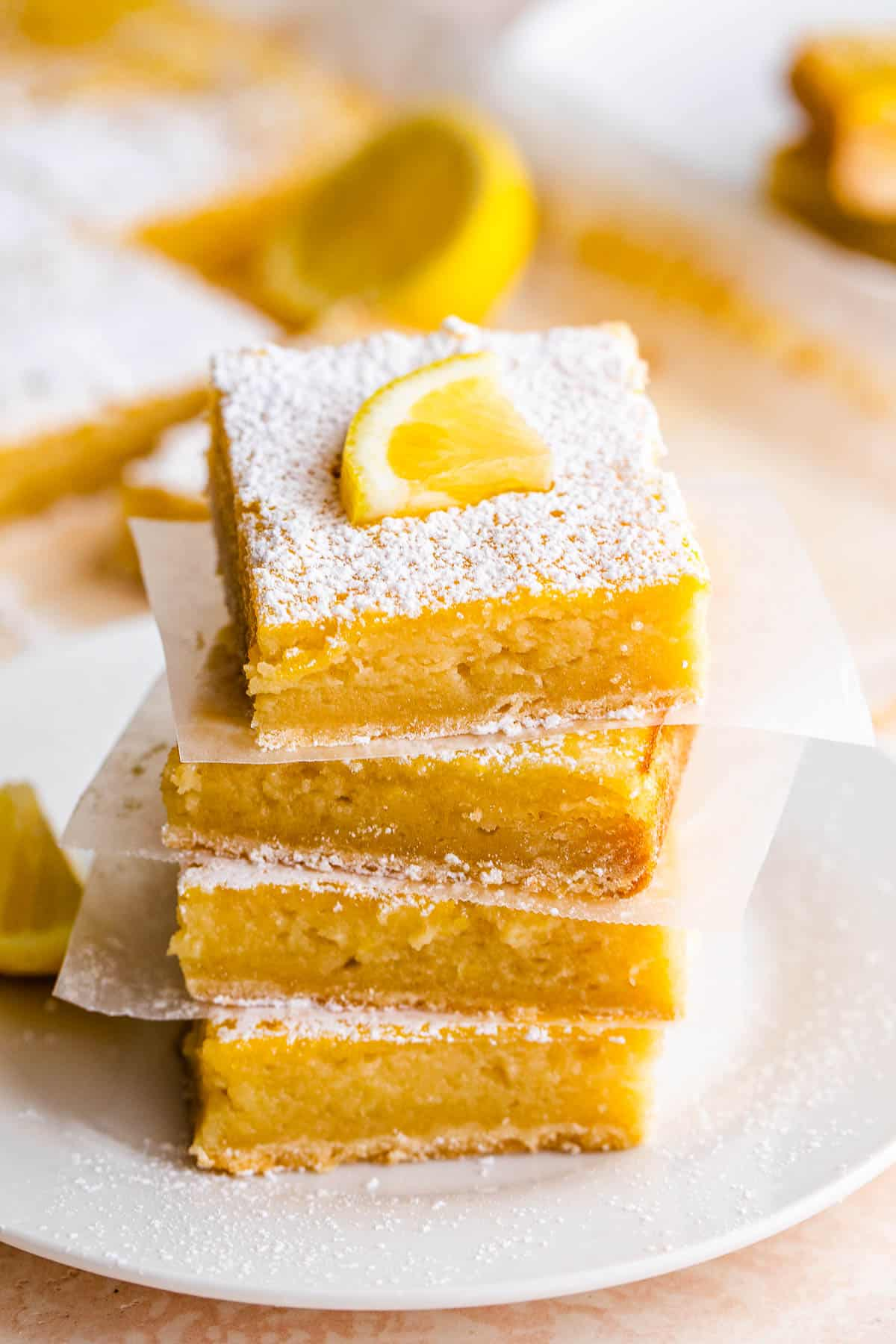 four lemon bars stacked one on top of the other and finished with a dusting of powdered sugar and a slice of lemon on top