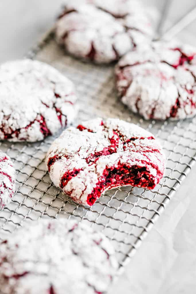 Six Red Velvet Crinkle Cookies on a Wire Cooling Rack with One Cookie Missing a Bite